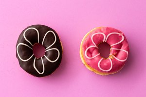 Pair of black and pink donuts isolated on colorful pink background