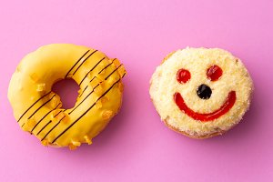 Close up of colorful and sweet donuts with one smiley face isolated on pink background