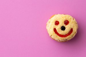 Close up flat lay of yellow smiley happy face donut isolated on pink background