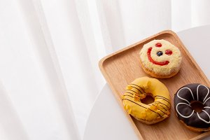 Close up of colorful and sweet donuts and one smiley face donut  near windows