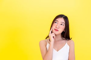 Asian beautiful woman thinking and considering with empty copy space over yellow background
