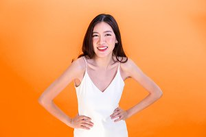 Asian cute woman posing arms akimbo or hands on hips isolated on orange background