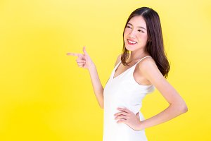 Asian cute woman pointing hands to  empty copy space and posing arms akimbo isolated on yellow background