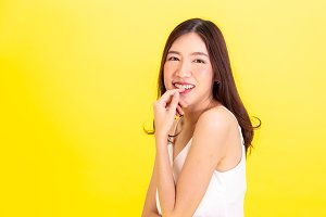 Portrait of attractive Asian smiling  woman showing cute expression and posture with isolated on yellow background