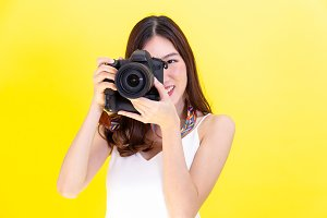 Attractive Asian woman holding a professional camera and taking photos over yellow background