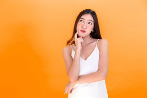 Portrait of attractive Asian smiling  woman showing cute expression and posture with isolated on orange background