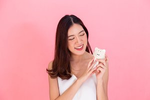 Portrait of young Asian woman holding a piggy bank, happy and excited over own saving isolated over vivid pink background