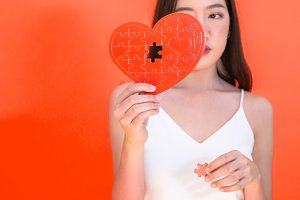 Portrait of attractive Asian woman holding red heart paper jigsaw isolated on pink red background