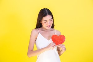 Portrait of attractive Asian smiling woman holding red heart paper jigsaw isolated on pink red background