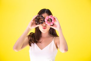 Attractive Asian woman holding two donuts with cute smiling expression over yellow background