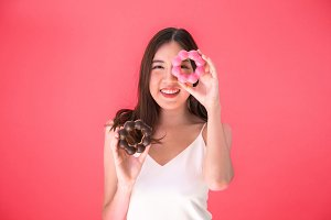 Attractive Asian woman holding two donuts with cute smiling expression over red pink background