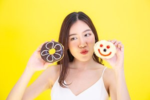 Attractive Asian woman holding two donuts with cute expression over yellow background