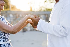 Mature couple hold hands in sunset