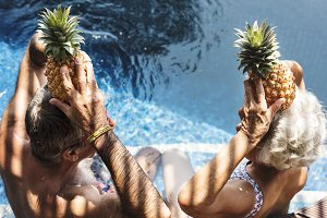 Couple hold pineapples above head