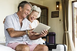 Senior couple using a tablet on bed