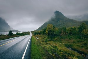 Scenic road along the coastline in Norway on a rainy and foggy day