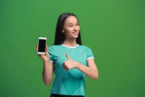 Portrait of a smiling woman showing blank smartphone screen