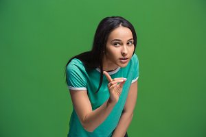 The young woman whispering a secret behind her hand over green background