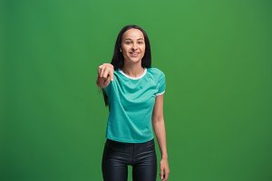 The happy business woman point you and want you, half length closeup portrait on green background.