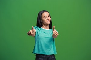 The happy business woman standing and smiling against green background.