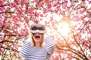 Woman wearing virtual reality goggles outside in spring nature