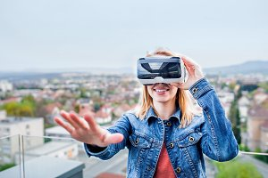 Woman wearing virtual reality goggles standing on a balcony