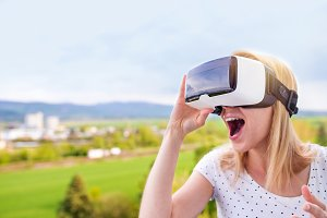 Woman wearing virtual reality goggles standing in a kitchen