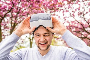 Man wearing virtual reality goggles outside in spring nature