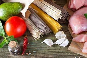 bunch of Italian spaghetti, noodles soba and sommel, chicken raw meat, avocado, zucchini with tomato on an old wooden background
