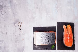 pieces of salmon fillet on dark slate cutting board. Lean proteins.