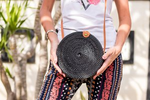 Woman hands with fashionable stylish black rattan bag. Tropical island of Bali, Indonesia. Rattan handbag.
