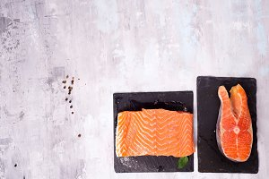 two fresh raw salmon steaks are laying on the dark slate board.