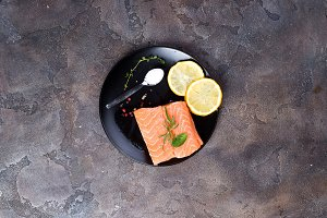 Salmon steaks on ice with lemon and salt on black plate. Lean proteins.