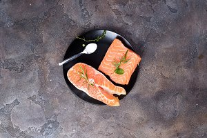 Salmon steaks on ice with salt on black plate. Lean proteins.