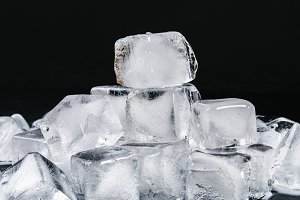Cubes of ice from water with mint leaves on a black background.