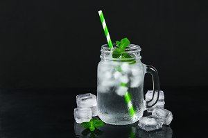 Ice water with ice and a mint leaf and a straw in a mason jar on a black background.