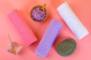 Spa on a pink pastel background. Towels, stones, aromamaslo, purple salt bath and pink flowers.