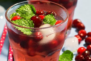 Close-up of a cranberry drink with ice and mint leaves. Selective focus