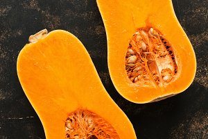 Halves of fresh raw pumpkin on a dark background. Sliced oval shaped pumpkin. The view from above, flat lay. Concept of autumn
