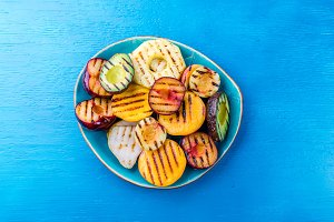 GRILLED FRUITS. Grill fruits - pineapple, peaches, plums, avocado, pear on blue plate. Blue background. Top view
