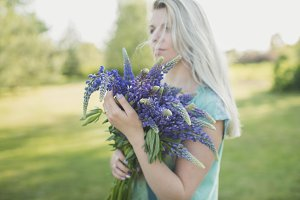 girl is standing with a bouquet
