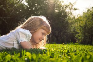 Portrait of a little girl. Sun, grass, summer. Child watching ladybug