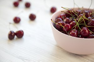Fresh cherries in a pink bowl