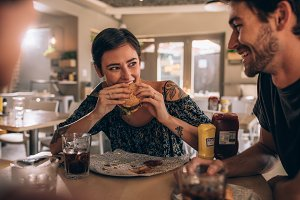 Woman eating burger with friends