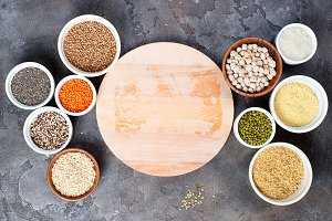 Superfoods and cereals selection in bowls with wooden board for your text on grey concrete background