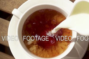 White porcelain cup on a saucer on a wooden table with a hot drink slow motion