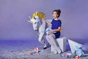 Child elegant blue dress. Beautiful little lady girl,fabulous unicorn near. Looks delight,admiration side,anticipation holiday. Fashion kid,advertising shop,purple,lilac background,copy space.