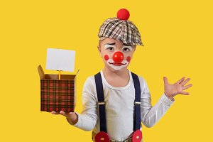 Little child clown in suit,make-up,red nose shows funny emotion face,surprise,sadness,uncertainty.Portrait kid boy joker,humorist,yellow background studio.In hand holds cardboard box,blank for text.