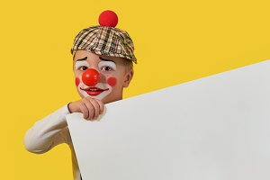 Funny child clown with blank white paper. Cute little boy clown in makeup,red nose. Little cheerful boy jester keep sheet with copy space for your text. Concept birthday, holiday,celebration, party.