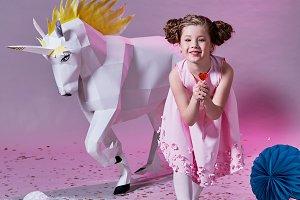 child fashion concept. romantic girl pink. eats a little lollipop. unicorn origami.
